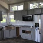 White Farmhouse Premier P577 with grey painted cabs, clerestory, and an optional island by Platinum Cottages. This custom built house was for an RRC Athens customer